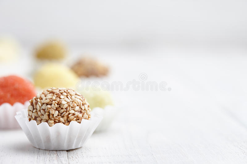 Handmade truffle chocolates. Chocolate truffle candies with sesame seeds on white wooden background royalty free stock photography
