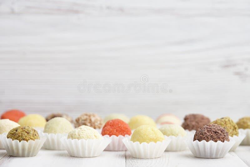 Handmade truffle chocolates. Chocolate truffle candies on white wooden background royalty free stock photos