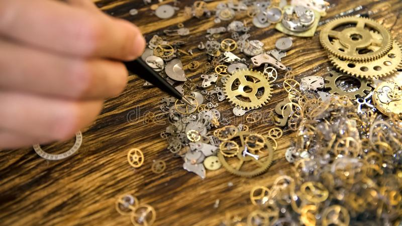 Watchmaker works at wooden table stock photo