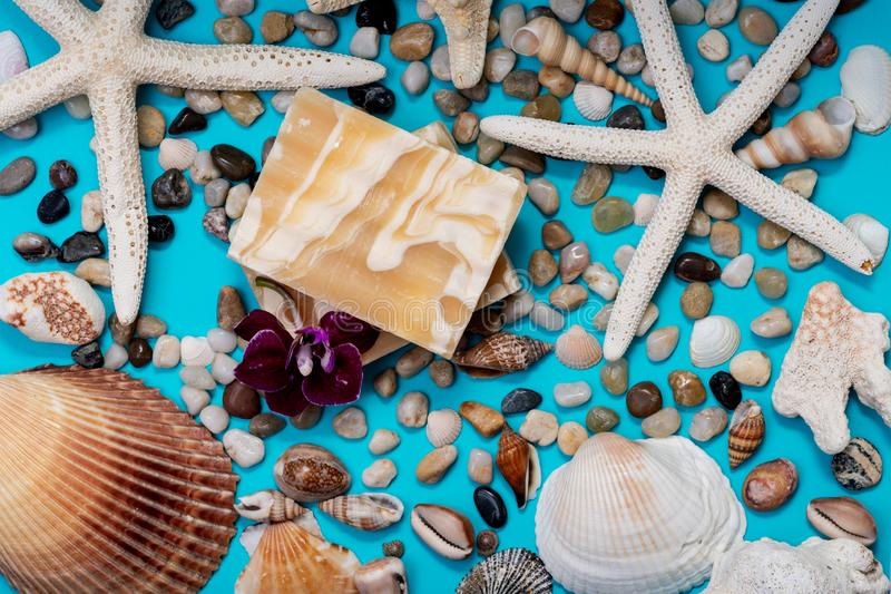 Handmade ultra-moisturizing Almond Scented Goat`s Milk Bar Soap decorated with Pebbles, Sea Stars, Sea Shells and Orchid Flower. On blue background stock photography