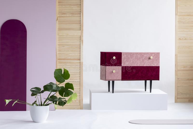 Handmade velvet pastel pink and burgundy commode in elegant white interior royalty free stock photography