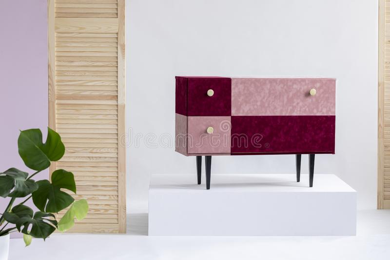 Handmade velvet pastel pink and burgundy commode in elegant white interior royalty free stock photos
