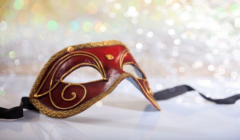 Handmade carnival mask on bokeh background. Handmade Venetian carnival mask on white surface, abstract bokeh background stock photo