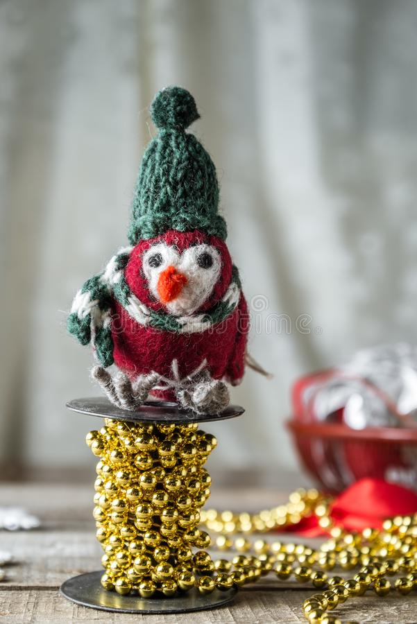 Handmade vintage Christmas toy bird clad in winter clothes on bobbin of golden colored beads. Handmade vintage Christmas toy bird clad in winter clothes perched stock photo