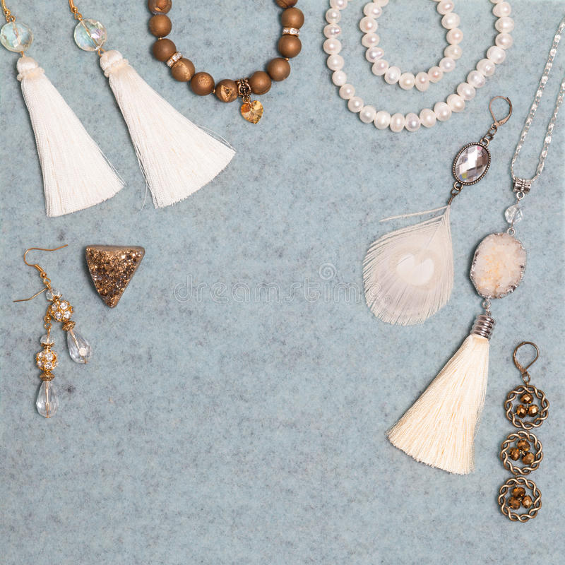 Handmade white and bronze jewelry on the gray woolen background stock photos