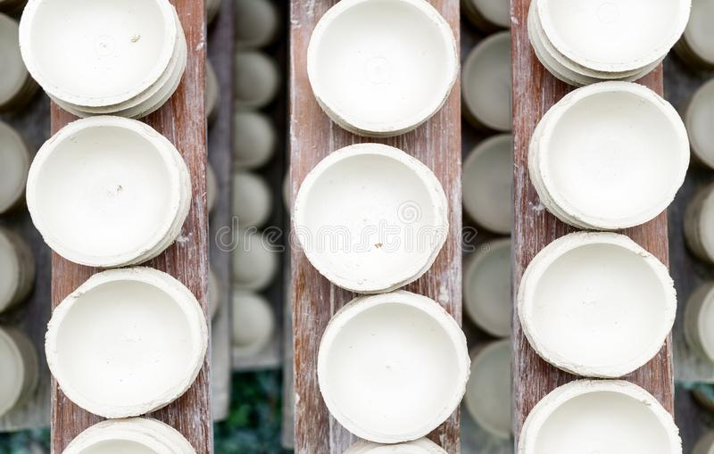 Handmade white clay pots dry on wooden planks. Top view. Workshop, manufactory stock image