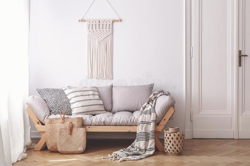 Handmade wicker bags on herringbone parquet floor of a warm living room interior with an artisan, beige macrame on a white wall. Concept stock images