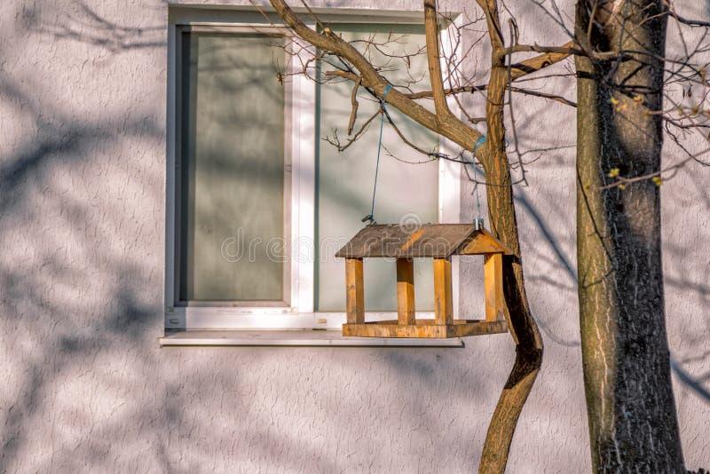 Handmade wooden bird feeder. Hanging on a tree near house stock photos
