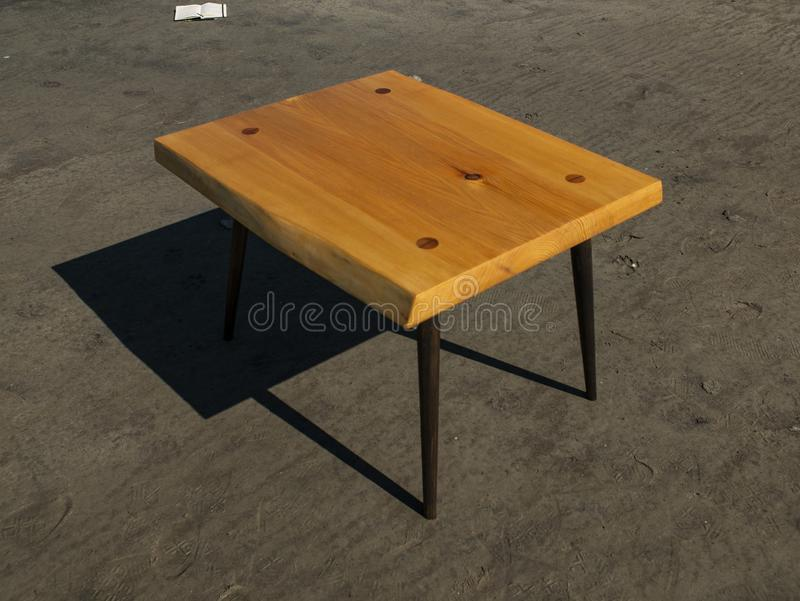 Handmade wooden coffee table stands on the sand. craftwork.  stock photos