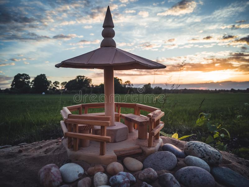 Handmade Wooden Shed Model on the Beach Sands with Stones In Front of it with Dramatic Sunset in Skies Behind it - Concept of. Harmony and Peace with a Space royalty free stock photo