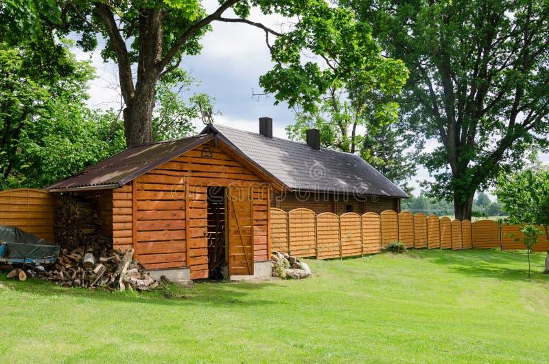 Handmade woodshed в деревне вдоль деревянной загородки стоковое изображение rf