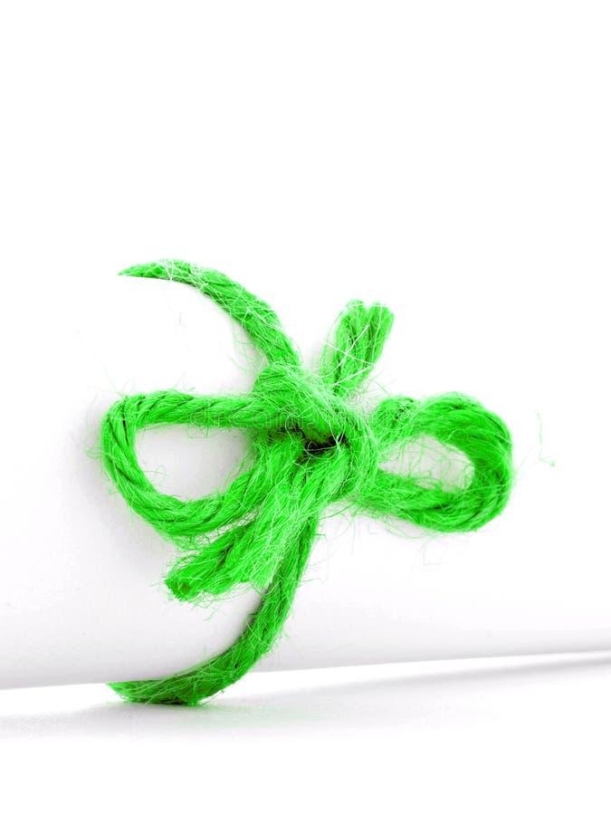 Handmade zielony linowy guzek wiązał na białego papieru ślimacznicie odizolowywającej zdjęcie royalty free