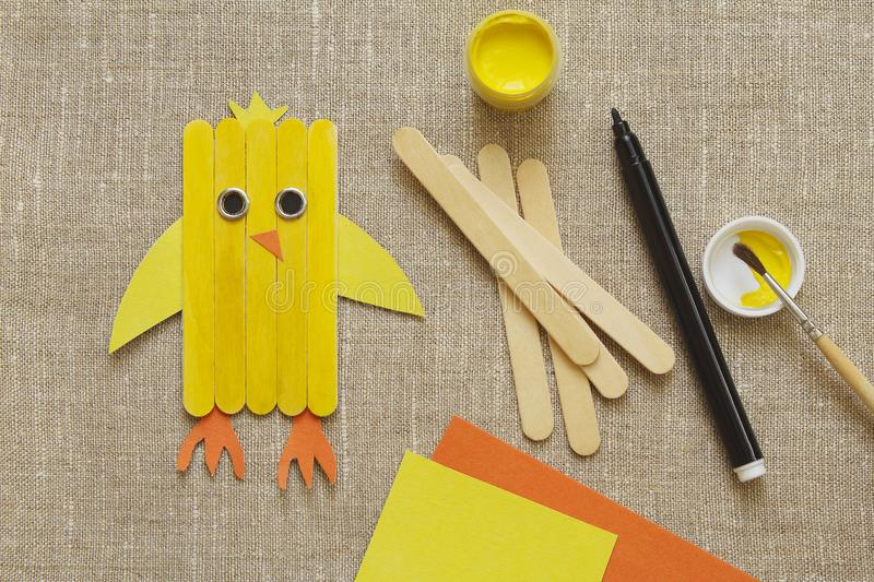 Handmake. Yellow chicken from wooden sticks on burlap. Homemade wooden stick chicken, tassel, colored paper and yellow paint on coarse homespun clothn royalty free stock image