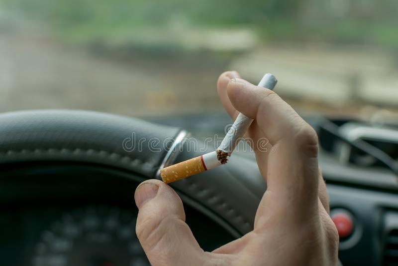 Handman som rymmer en bruten cigarett royaltyfri bild