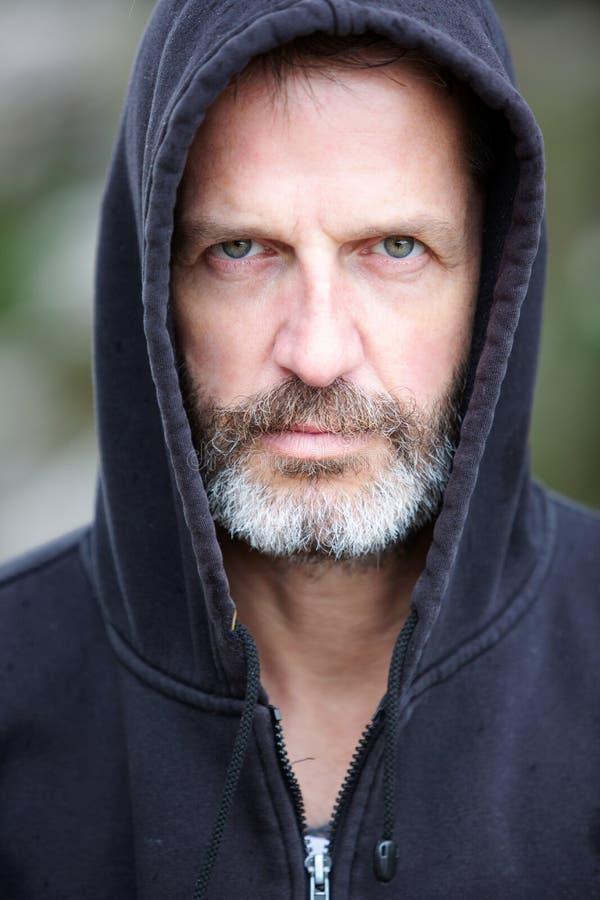 Handome bearded man wearing a hood stock photo