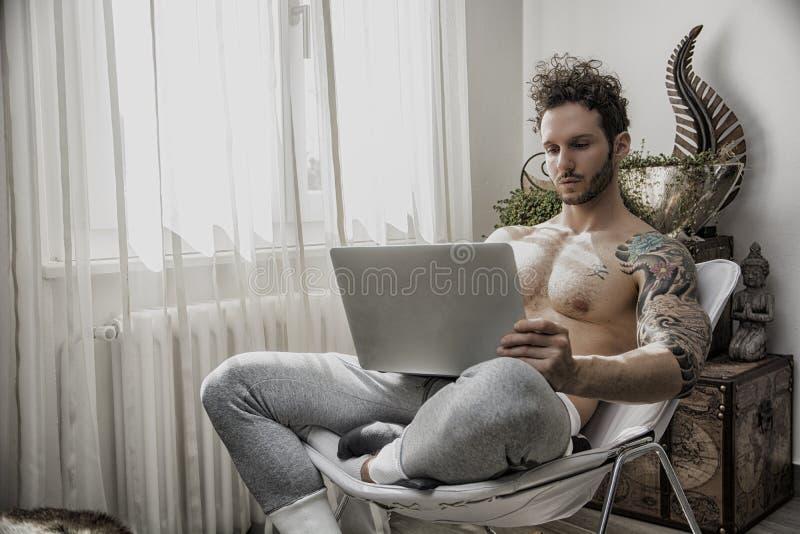 Handosme人在家与计算机一起使用 免版税图库摄影