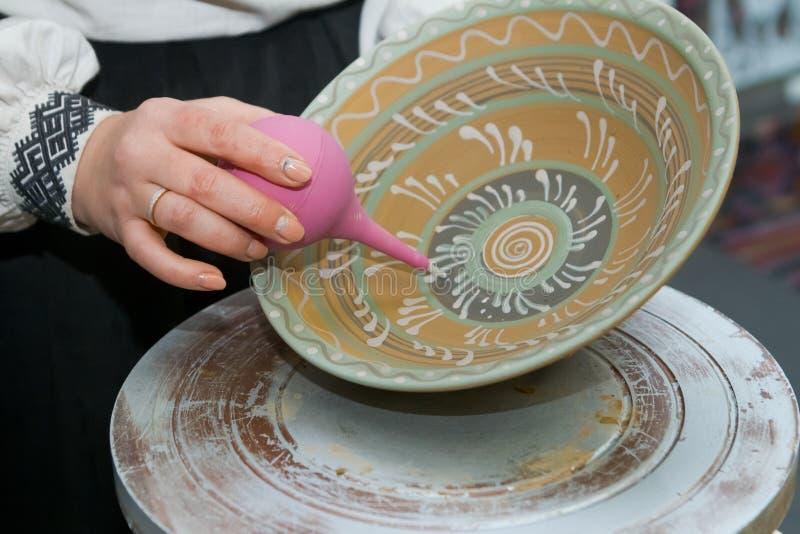 Handpainting de plat décoratif fait main d'argile, la main de l'artisan peint un modèle traditionnel avec le lavement, style de p photos stock