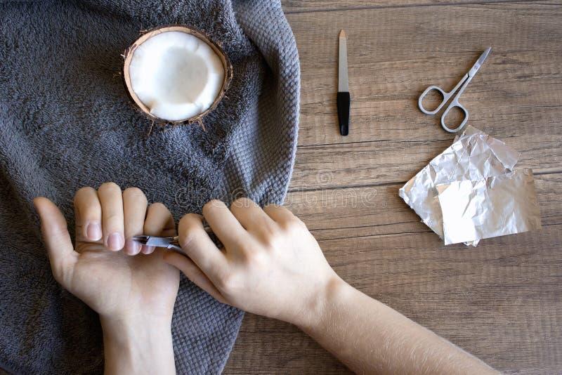 Handpflege, Volkshandpflege Maniküre mit Kokosnussöl, Manikürewerkzeuge: Scheren, Nagelfeile Vereiteln Sie Gel-polnischen Entfern stockbilder