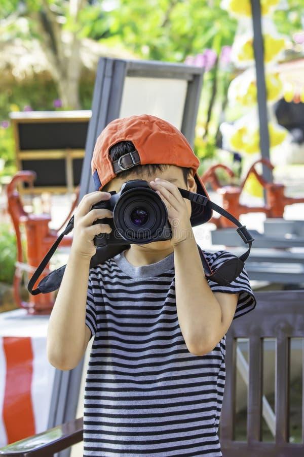 Handpojken som rymmer kameran som tar bilder parkerar in royaltyfria foton