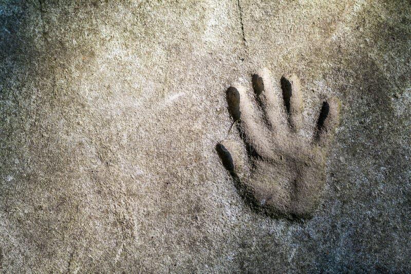 Handprint memorable de una mano en un muro de cemento viejo fotos de archivo libres de regalías