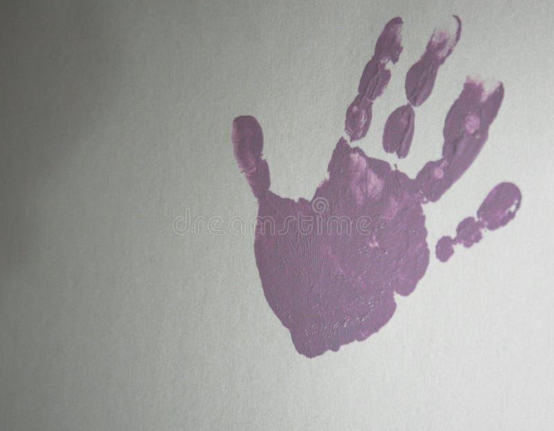 Handprint rosado de una mano en un fondo blanco de la cartulina foto de archivo libre de regalías