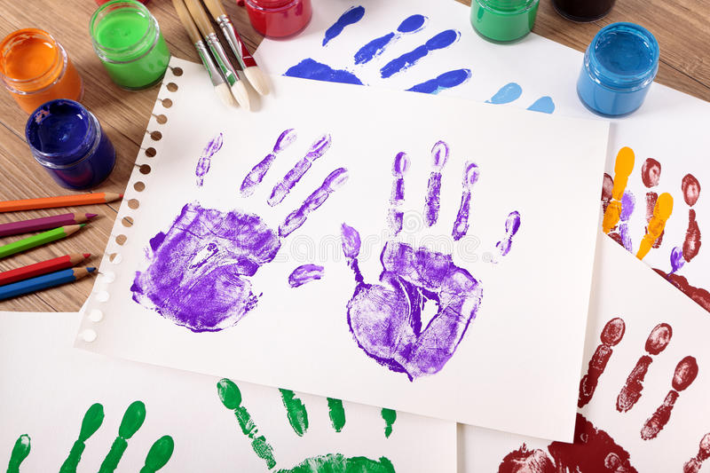 Handprints and art equipment, painting class, school desk. Painted handprints with art and craft equipment on a school table stock photos