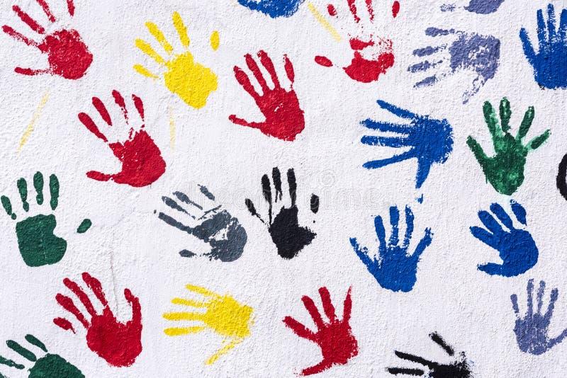 Handprints i gult, blått, rött, grönt, svärtar på en vit vägg, bakgrund royaltyfri illustrationer