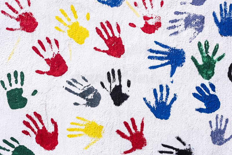 Handprints w kolorze żółtym, błękit, czerwień, zieleń, czarna na białej ścianie, tło royalty ilustracja