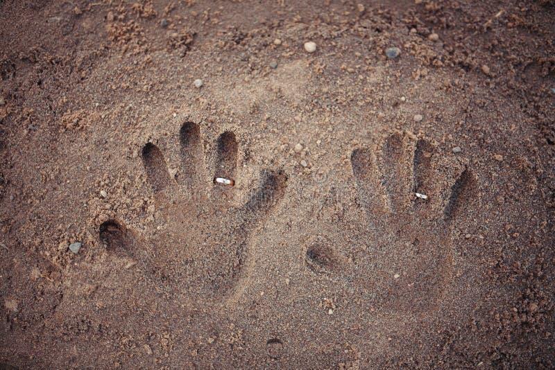 Handprints y recienes casados de los anillos en la arena foto de archivo
