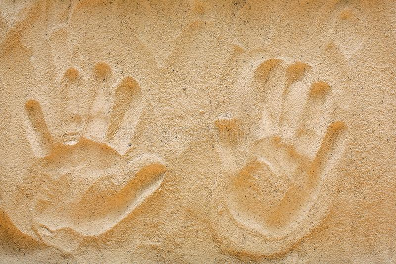 Handprints on yellow beach sand, top view royalty free stock photo