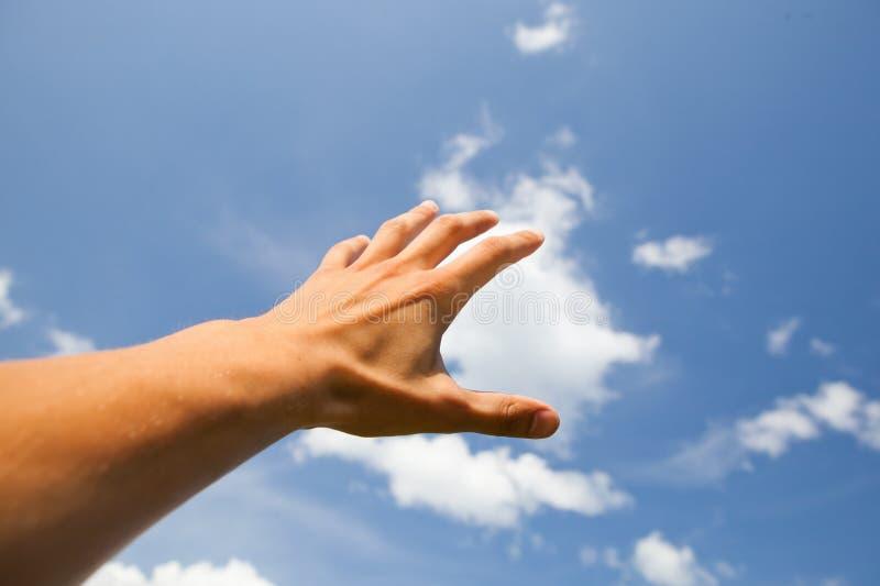 Handreichweite für den Himmel stockbild