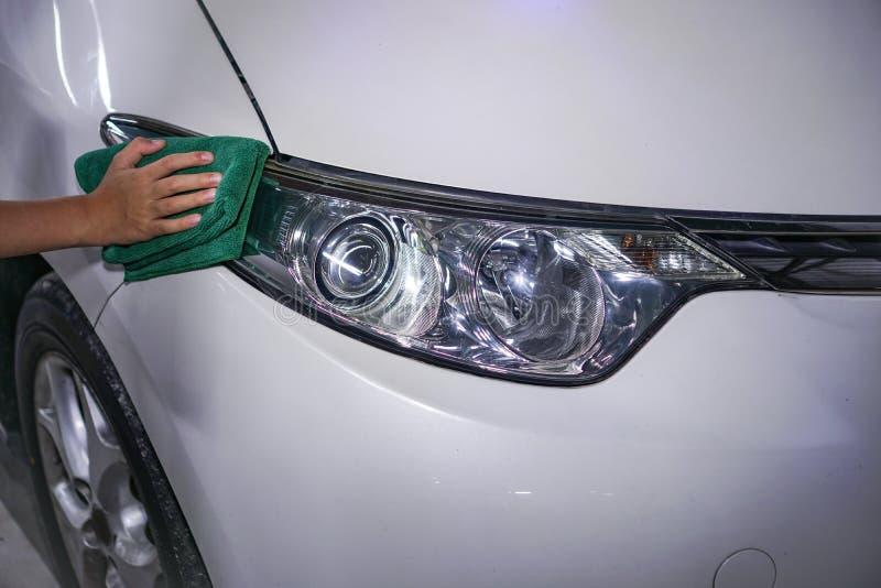 Handreinigungsautoscheinwerfer auf einem weißen Auto lizenzfreie stockfotos