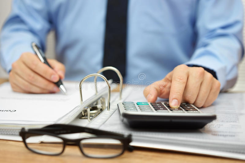 Hands of accountant with calculator,documentation and pen. Accounting concept stock image
