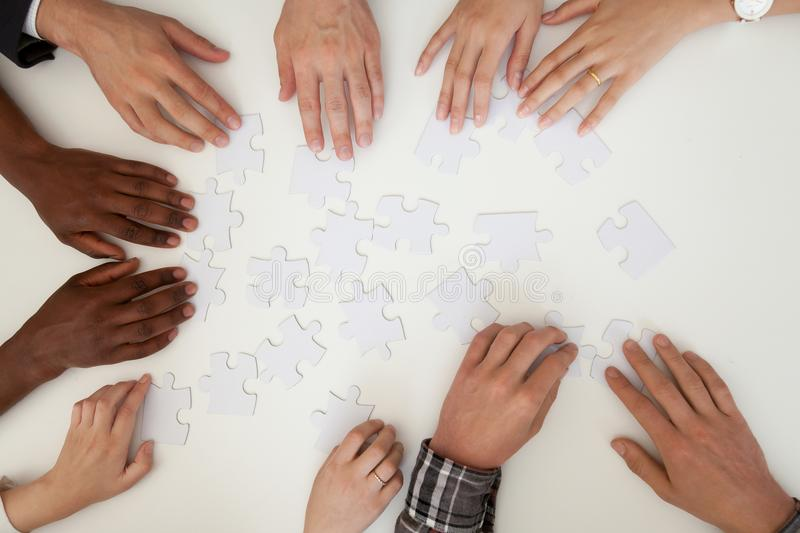 Hands of multiracial people assembling puzzle, top close up view royalty free stock photos