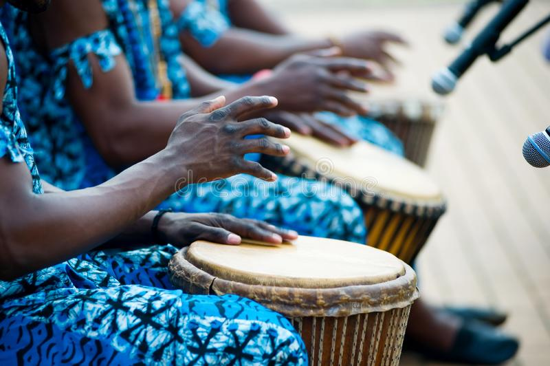 Hands of African drummers in blue costumes and traditional drums stock photography