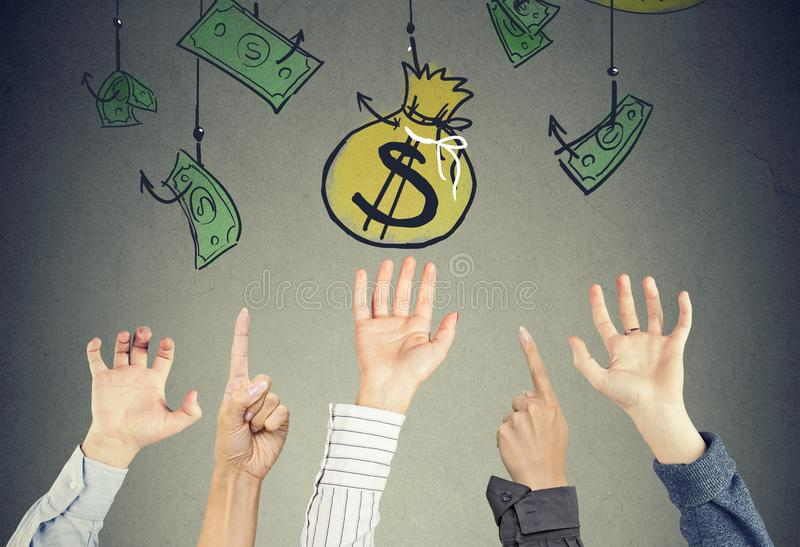Hands in the air trying to reach money bag hanging on the hooks stock photos