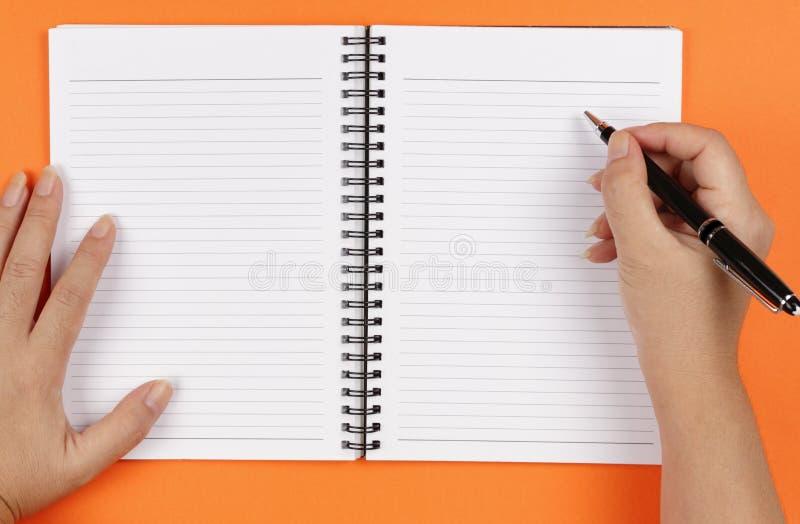 hands anteckningsbokpennan arkivbild