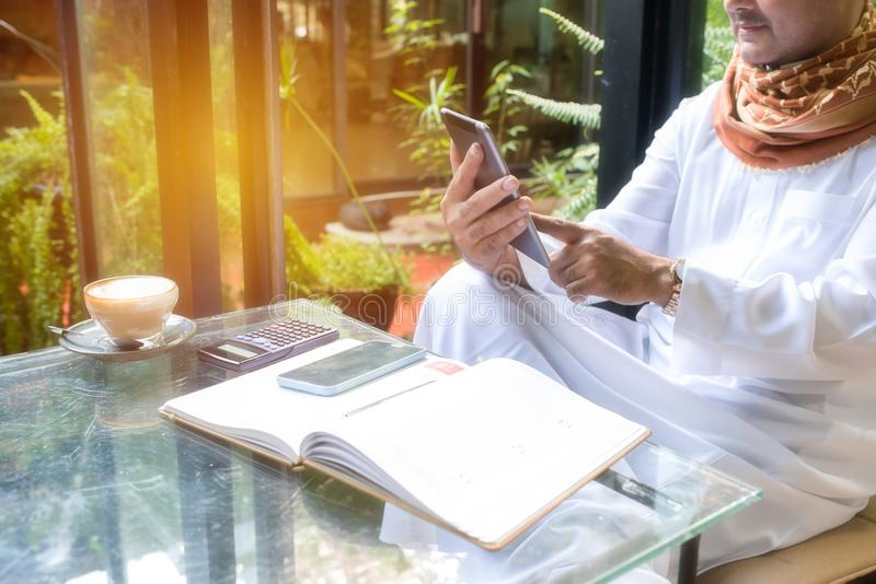 Hands of Arab muslim business man use tablet while sit in coffee. Shop,smart phone ,calculator and notebook on gladd table.Freelance lifestyle no working space stock photo