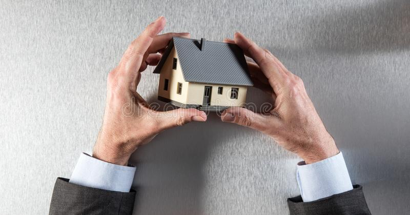 Hands of architect or businessman holding house for home valuation stock image
