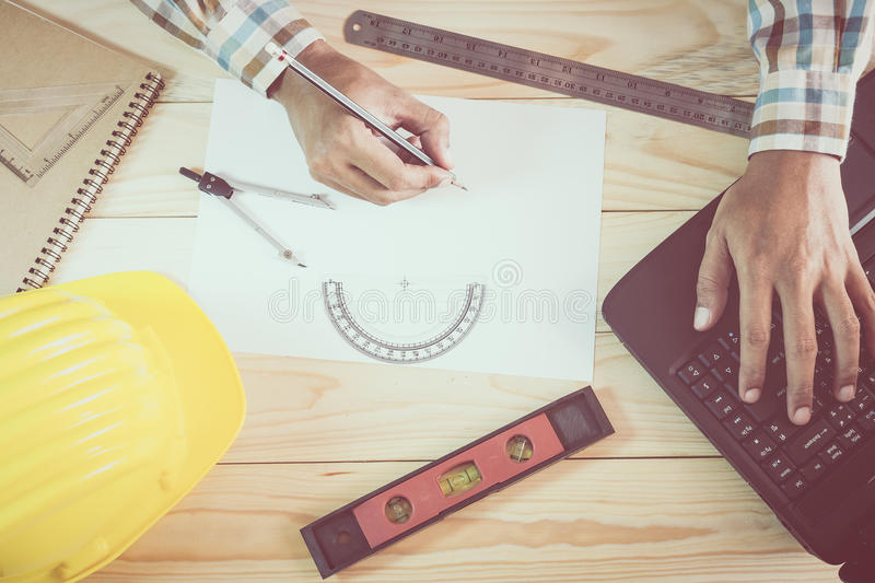 Hands of architect working on wooden desk. Hands of architect working with laptop on wooden desk royalty free stock photography