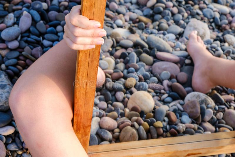 Hands, arms, legs and feet of a young woman appear from behind a mirror on a bed of boulders. royalty free stock photos