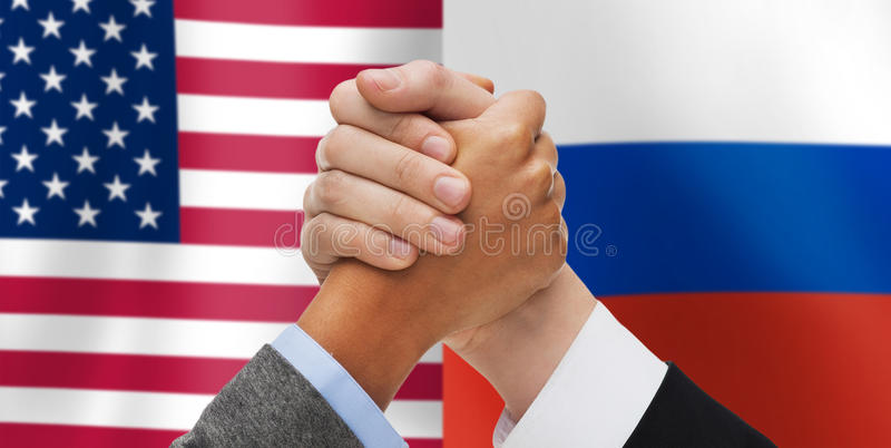 Hands armwrestling over american and russian flags. Partnership, politics, gesture and people concept - close up of two hands armwrestling over american and stock photo