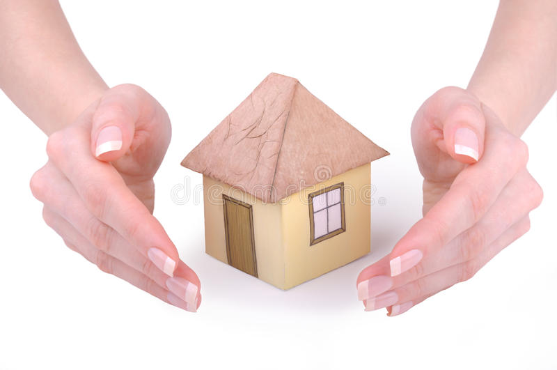 Hands around model house. Female hands around paper model house, isolated on white background stock photos