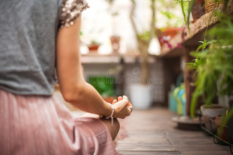 Hands asana yoga. The girl practices yoga in flowers at home close-up. Meditation, hands, bracelet handmade. Hands asana yoga. The girl practices yoga in flowers stock photos