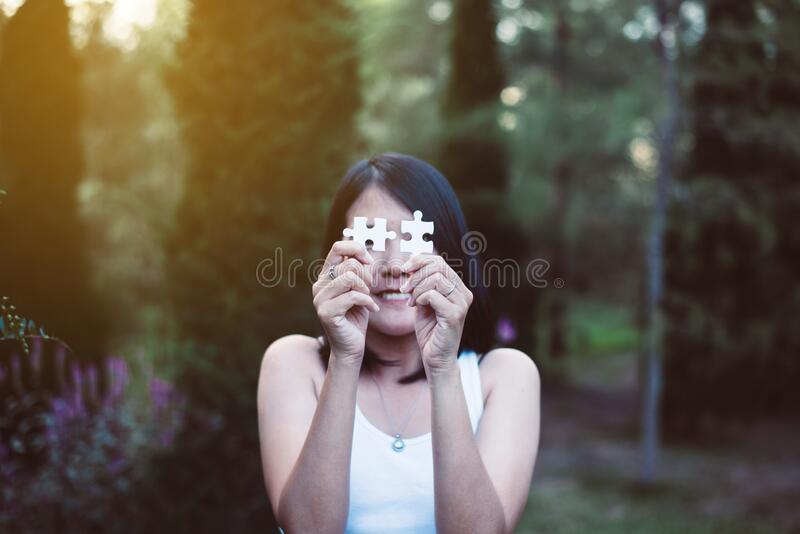 Hands asian woman connect couple puzzle piece together with sun light background,Business success and strategy concept,Close up stock images