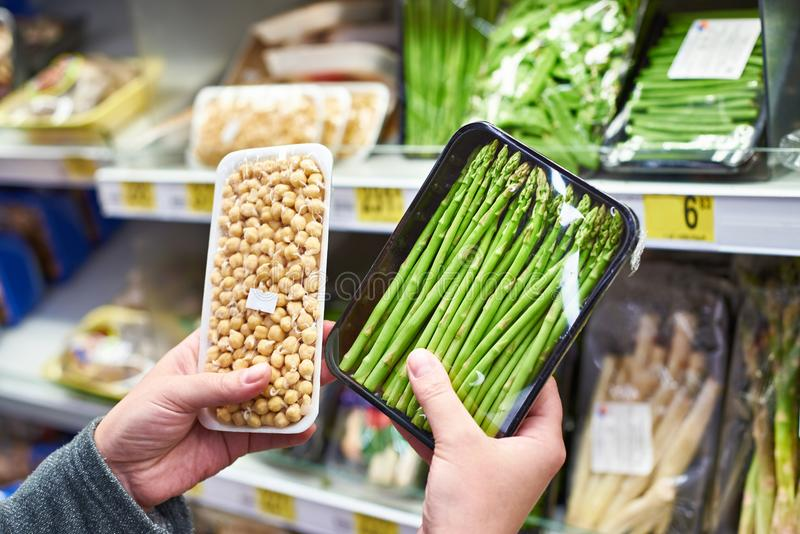 Hands with asparagus and sprouted peas in shop stock image