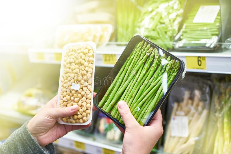 Hands with asparagus and sprouted peas in shop. Buyers hands with asparagus and sprouted peas in shop stock images
