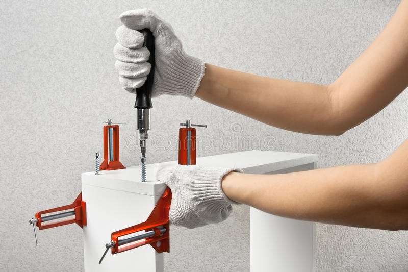 Hands assembling furniture with screwdriver stock photography