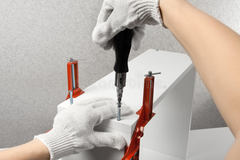 Hands assembling furniture with screwdriver royalty free stock photos