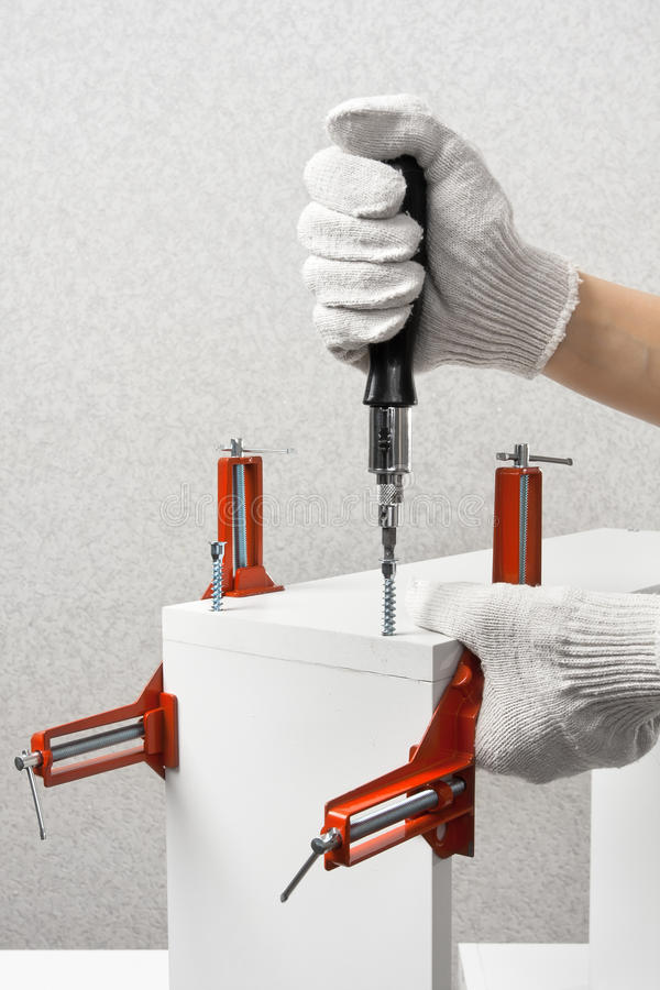 Hands assembling new furniture with screwdriver royalty free stock images